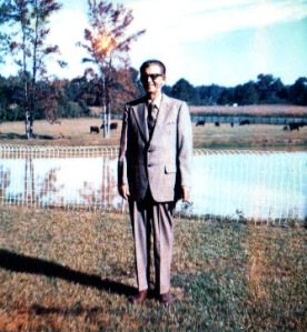 Here's a picture of how I best remember Papa.  He's smiling and standing in front of his house with his cattle and the pond in the background.