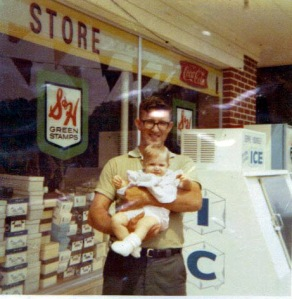 "You can see part of the ""Save More..."" sign at the top of the window, behind Dad and me."