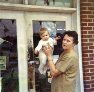 Aunt Dossie is holding me (7 months old). Can you see the 'Shop at' at the top of the glass doors?  Looks like the old door could use a paint job!